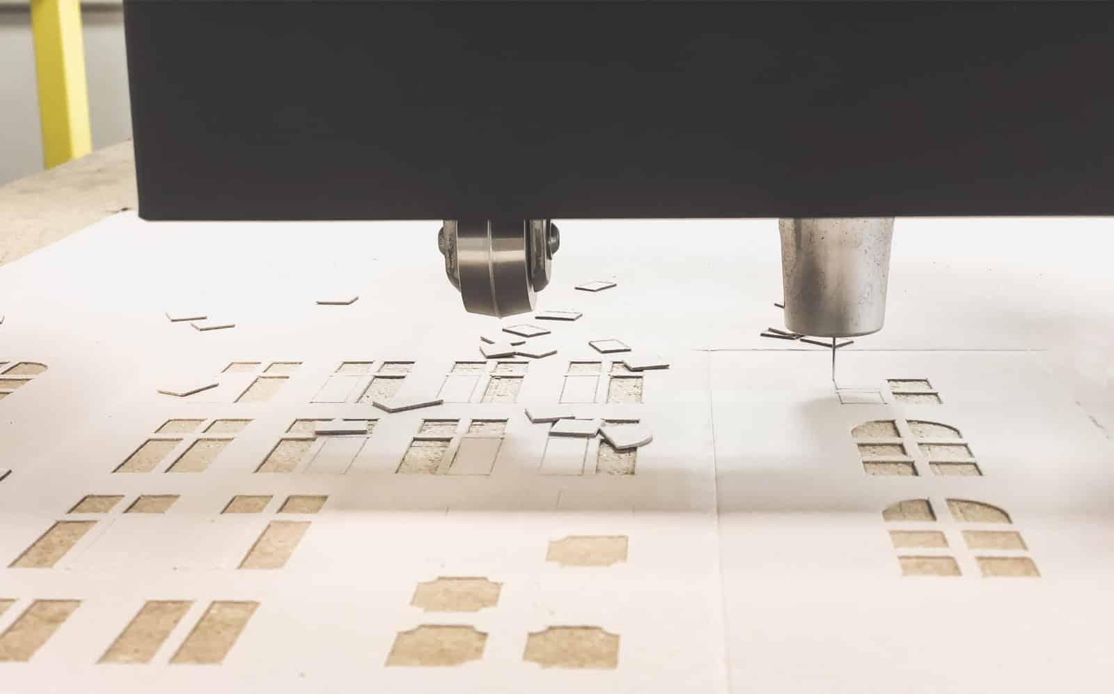 Maszyna CNC w pracowni Architected Sound wycina po obrysie kartonowe lampiony kamieniczki